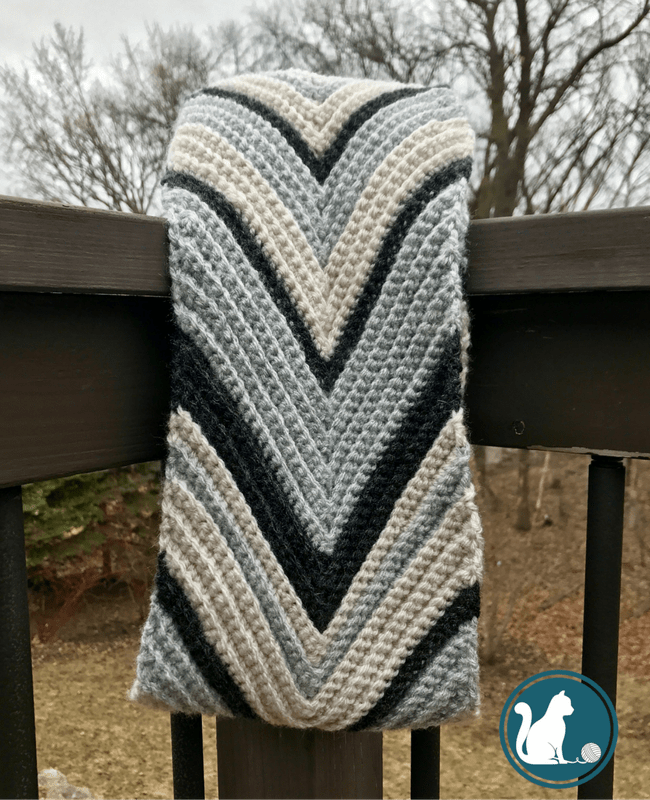 striped chevron crochet scarf hanging off a railing