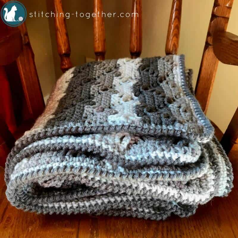 crochet baby blanket folded on a rocking chair