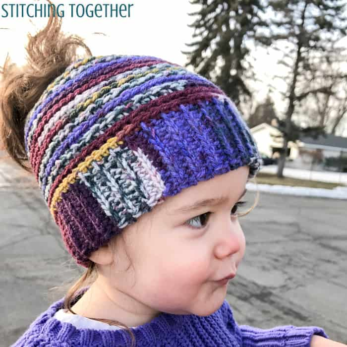 toddler girl wearing a multicolored crochet toddler hat