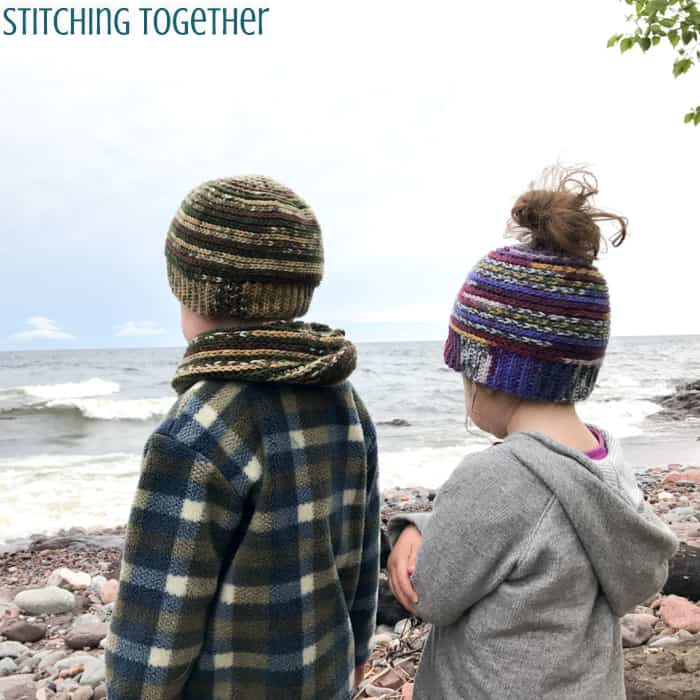 2 kids wearing crochet toddler hats while looking out over the water