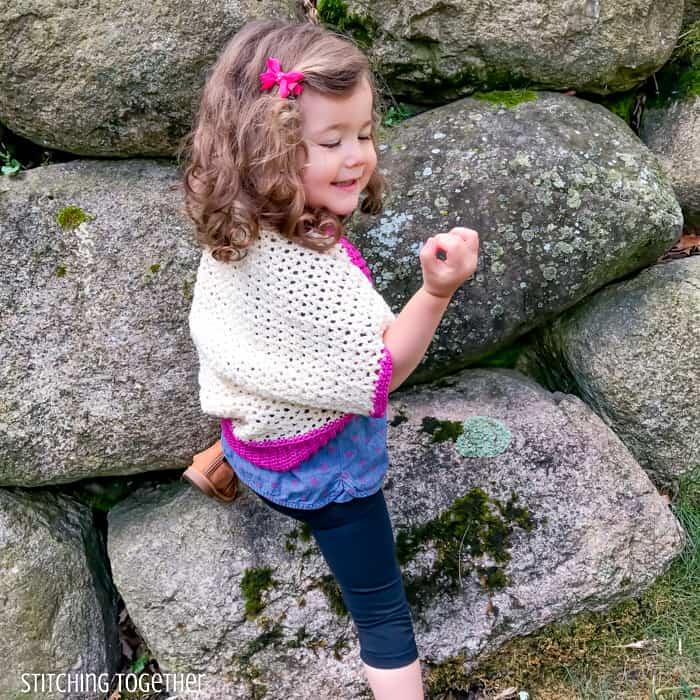 girl showing back of toddler cocoon shrug crochet