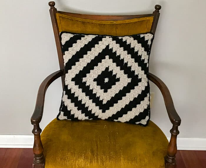 geometric crochet pillow in black and ivory still on a yellow chair