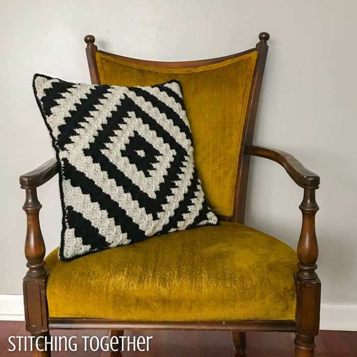 modern crochet pillow in black and ivory still on a yellow chair