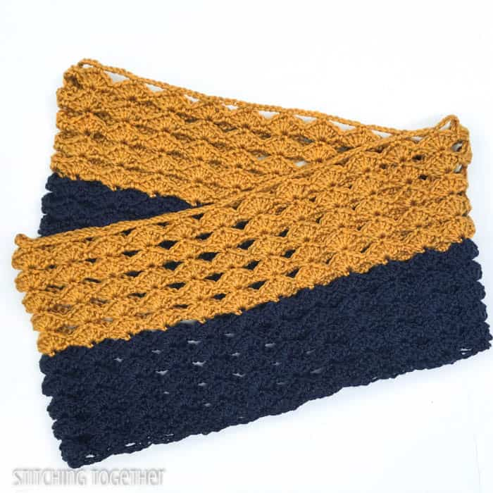 a folded color block crochet infinity scarf in gold and blue with shell stitches
