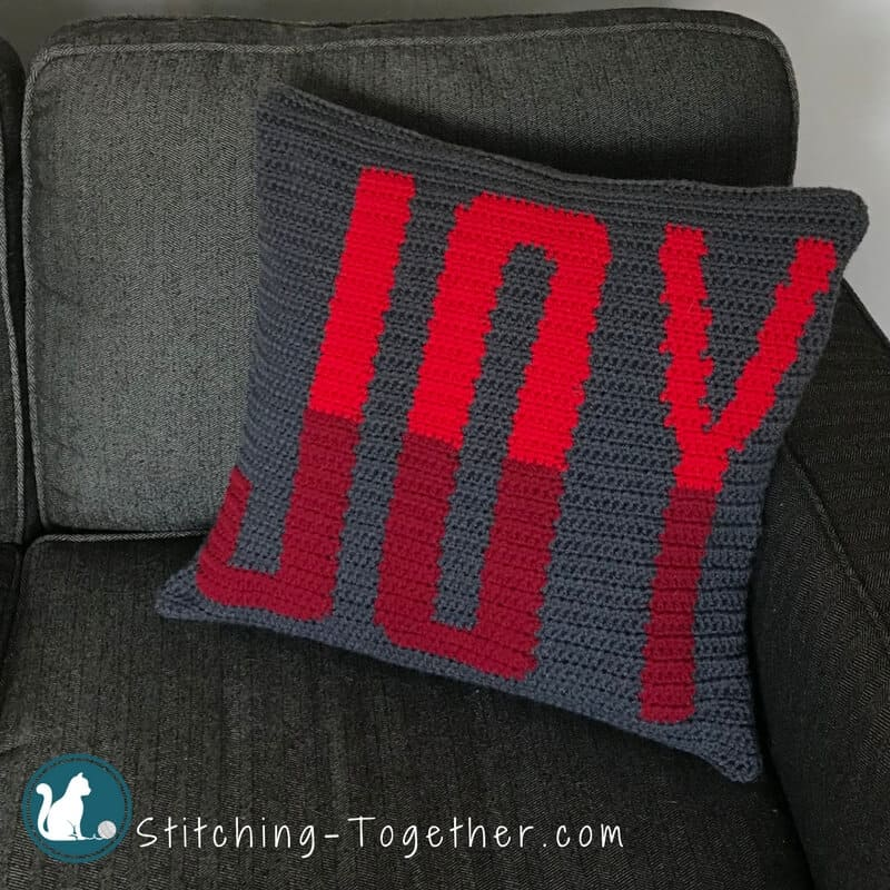 Crochet Pillow with the word joy in red sitting on a couch