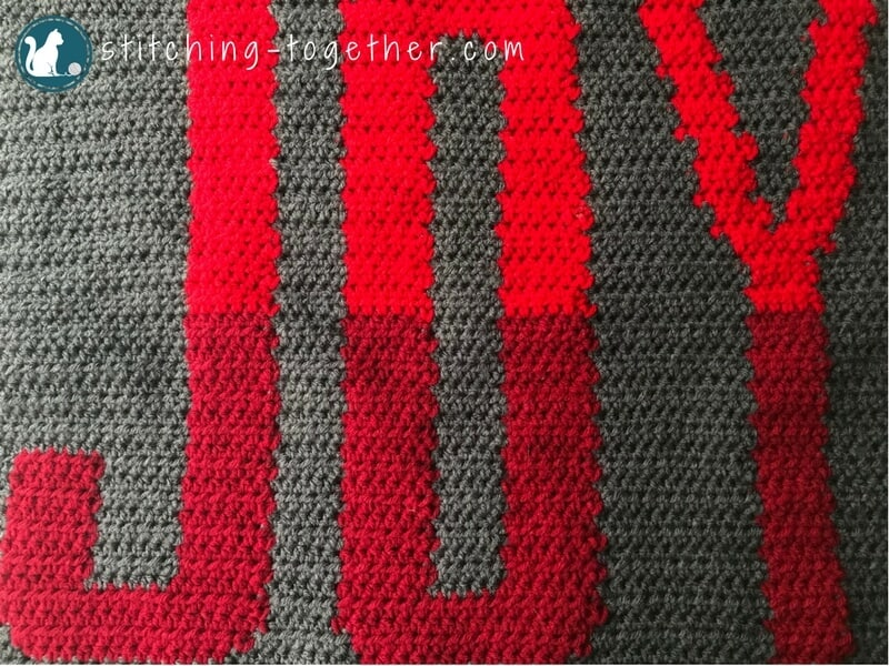Close up of word Joy in gray crochet background
