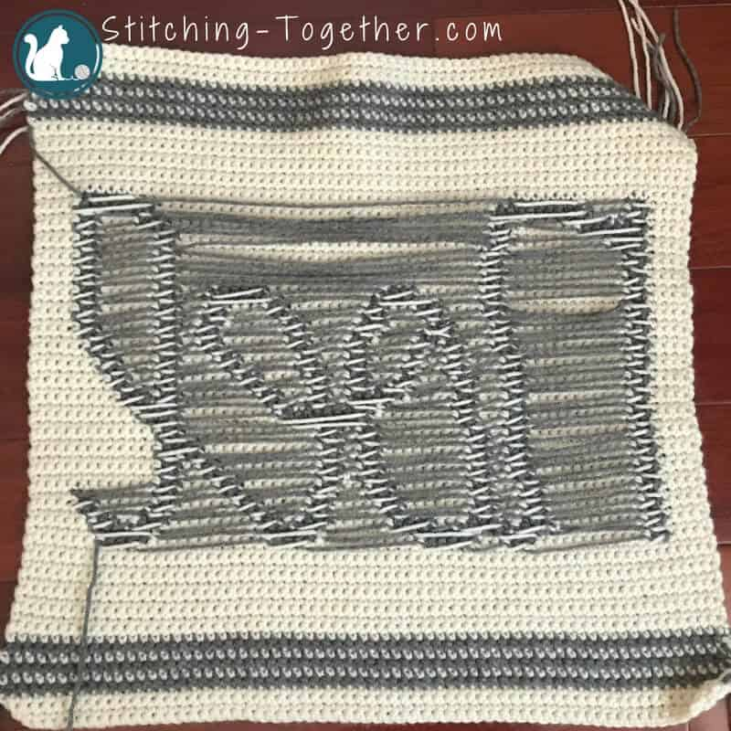 backside of crochet pillow showing yarn