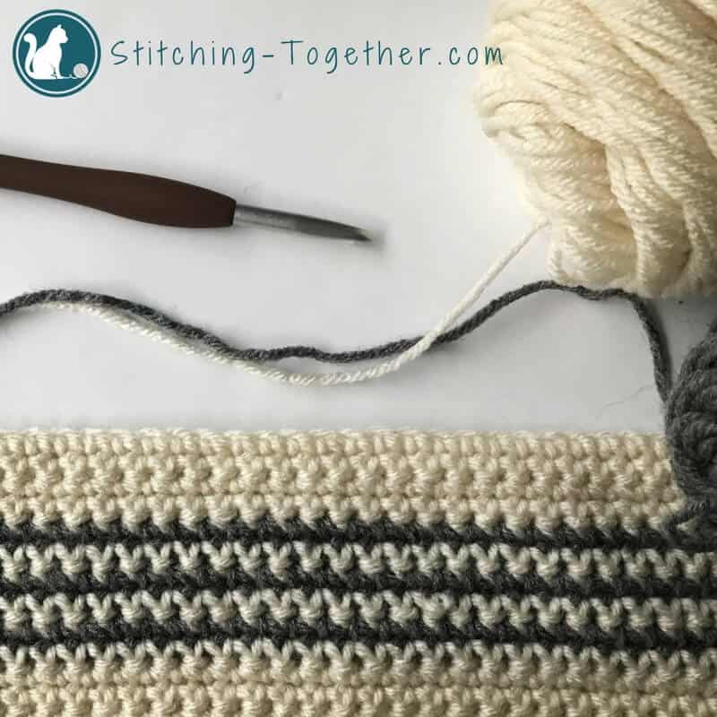 gray and off white crochet stripes in process with crochet hook