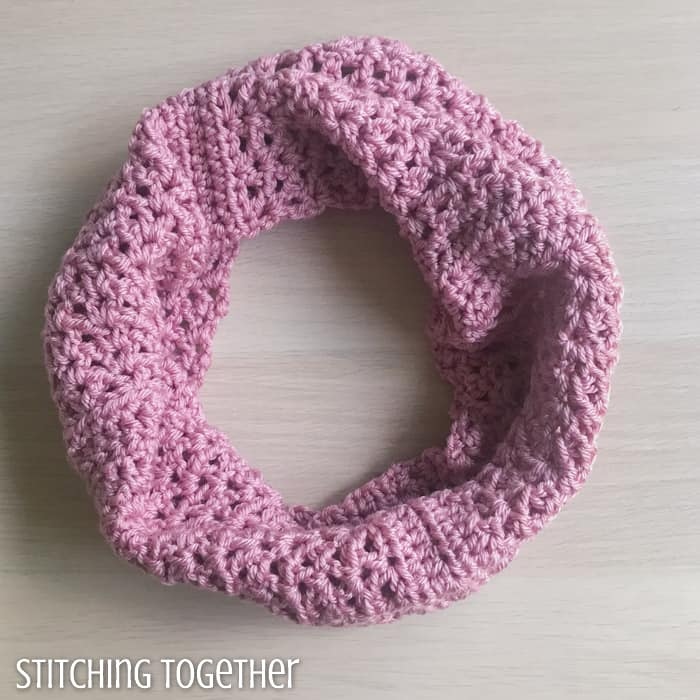 pink crochet cowl with open stitches sitting on a surface