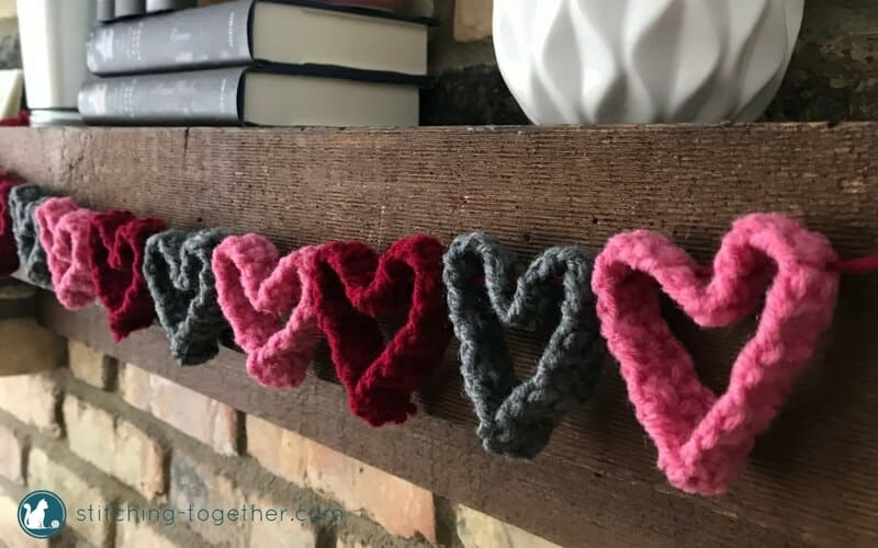crochet heart garland close up from side hanging on mantel
