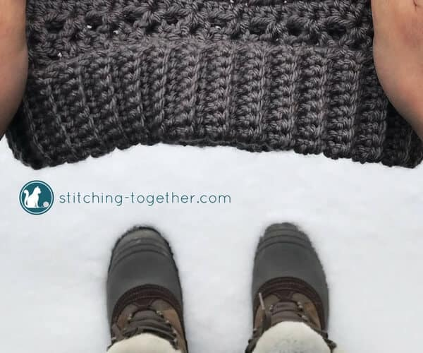 hands holding a crochet hat over the snow with boots visible