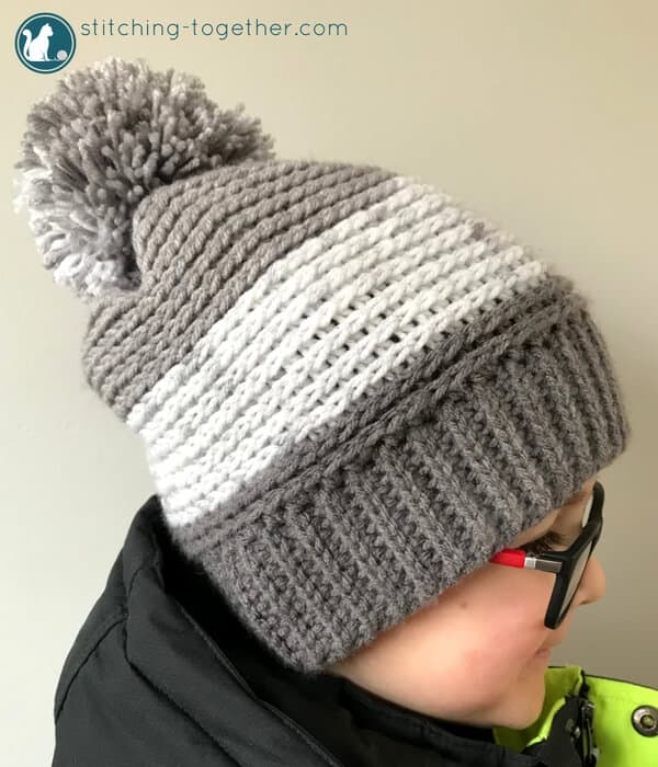 Gray and white crochet slouchy hat with brim and pom pom on kid