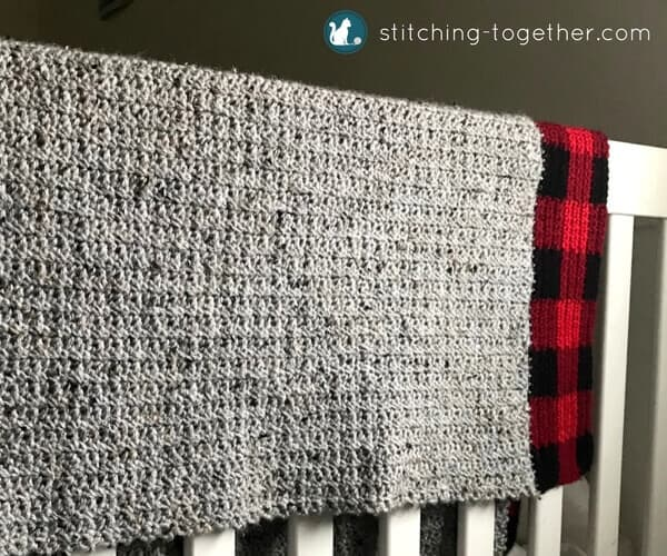 Gray baby blanket with buffalo plaid border draped on the side of a crib