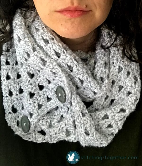Gray crochet scarf with lacy pattern of open triangle stitches