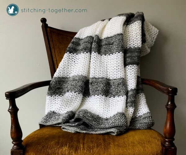 gray and white v stitch crochet blanket draped on yellow chair