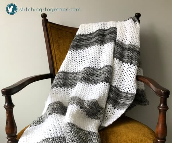 White and gray striped v stitch crochet blanket on chair