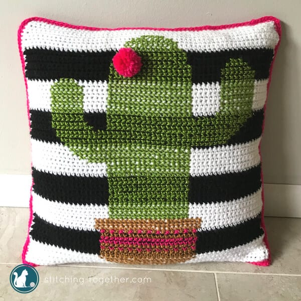 black and white striped crochet pillow with cross stitch cactus