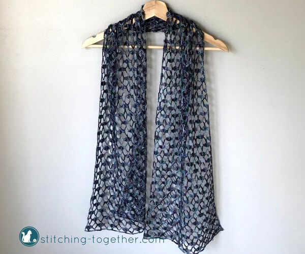 purple lacy crochet scarf draped on a hanger