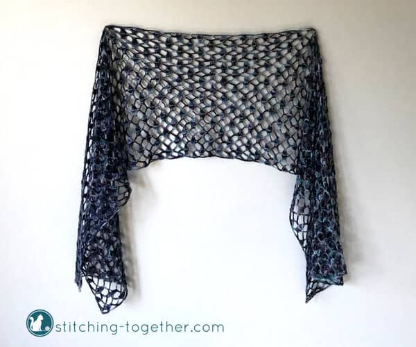 lacy crochet scarf with open shell stitches hanging on a wall