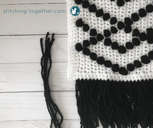 white crochet fabric with black puff stitches and fringe