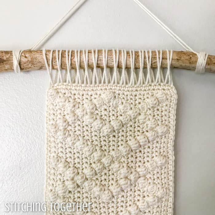 close up of neutral crochet wall hanging with bobbles