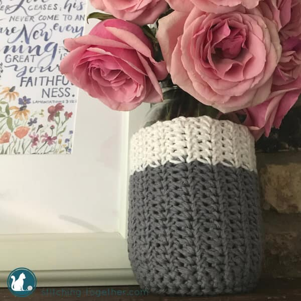 gray and white crochet mason jar cozy holding pink roses