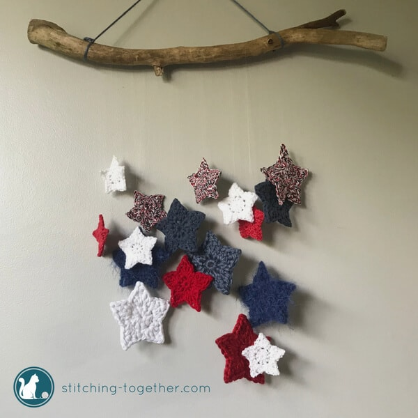 crochet stars hanging from a wood branch