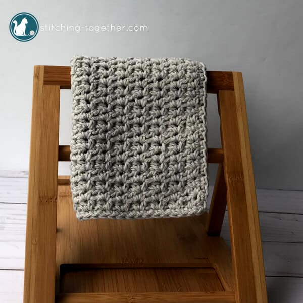 gray crochet washcloth hanging on bamboo rack