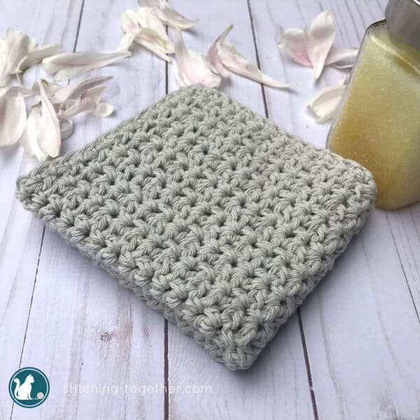 folded simple crochet washcloth with flower petals and body scrub