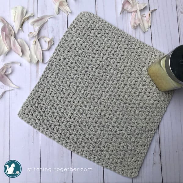 neutral crochet washcloth laying flat surround by petals