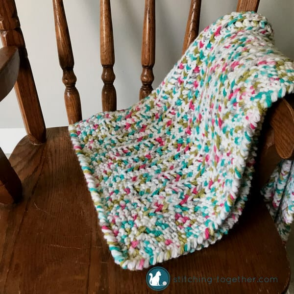 crib blanket on small chair with colors for a girl