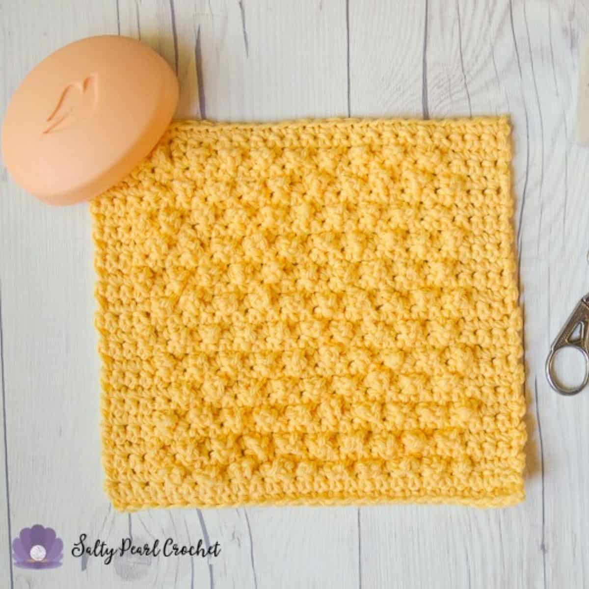 yellow crochet dishcloth laying flat with a bar of soap on top