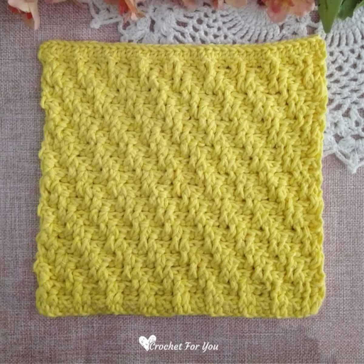 yellow crochet square dishcloth with raised stitches