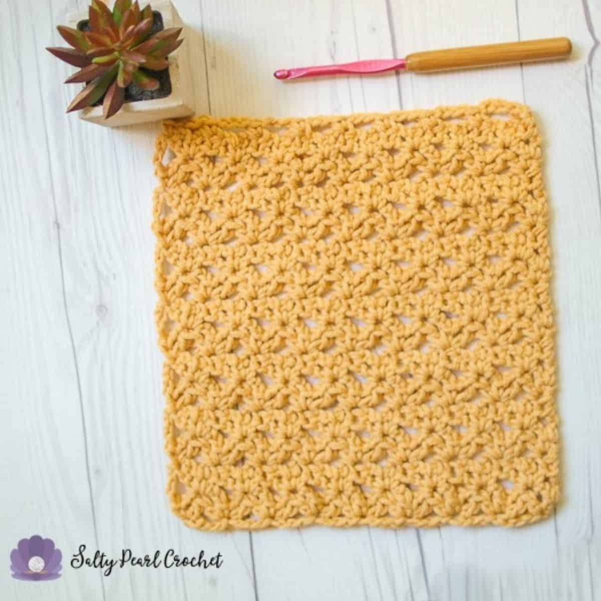 yellow crochet washcloth laying flat next to a plant and a crochet hook