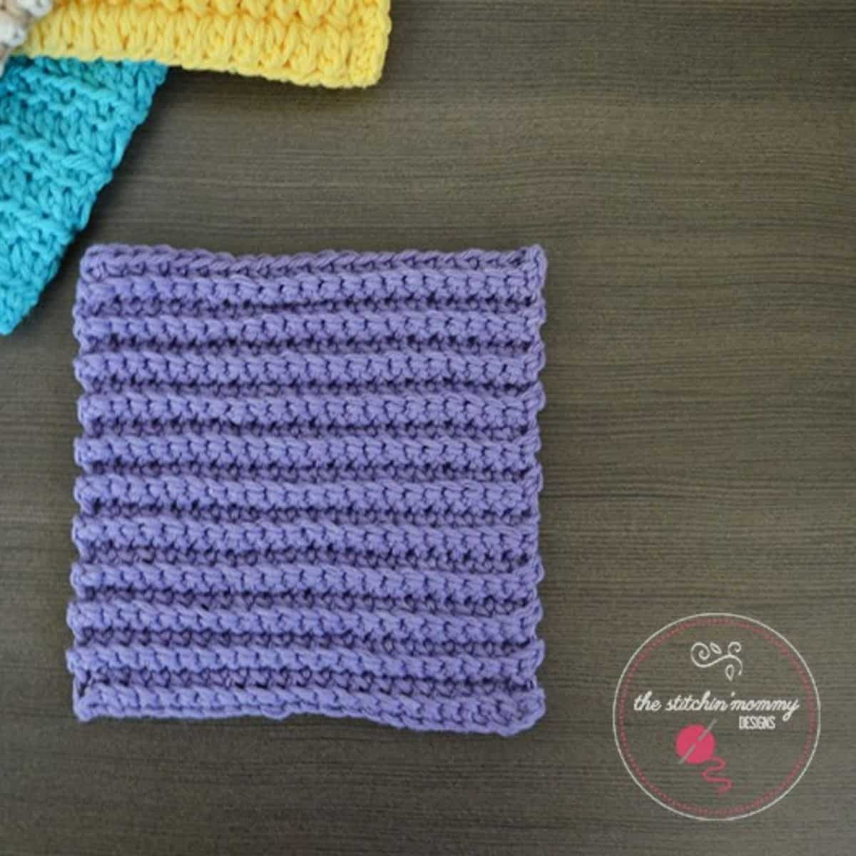 ribbed dishcloth laying flat with other dishcloths peeking from the corner