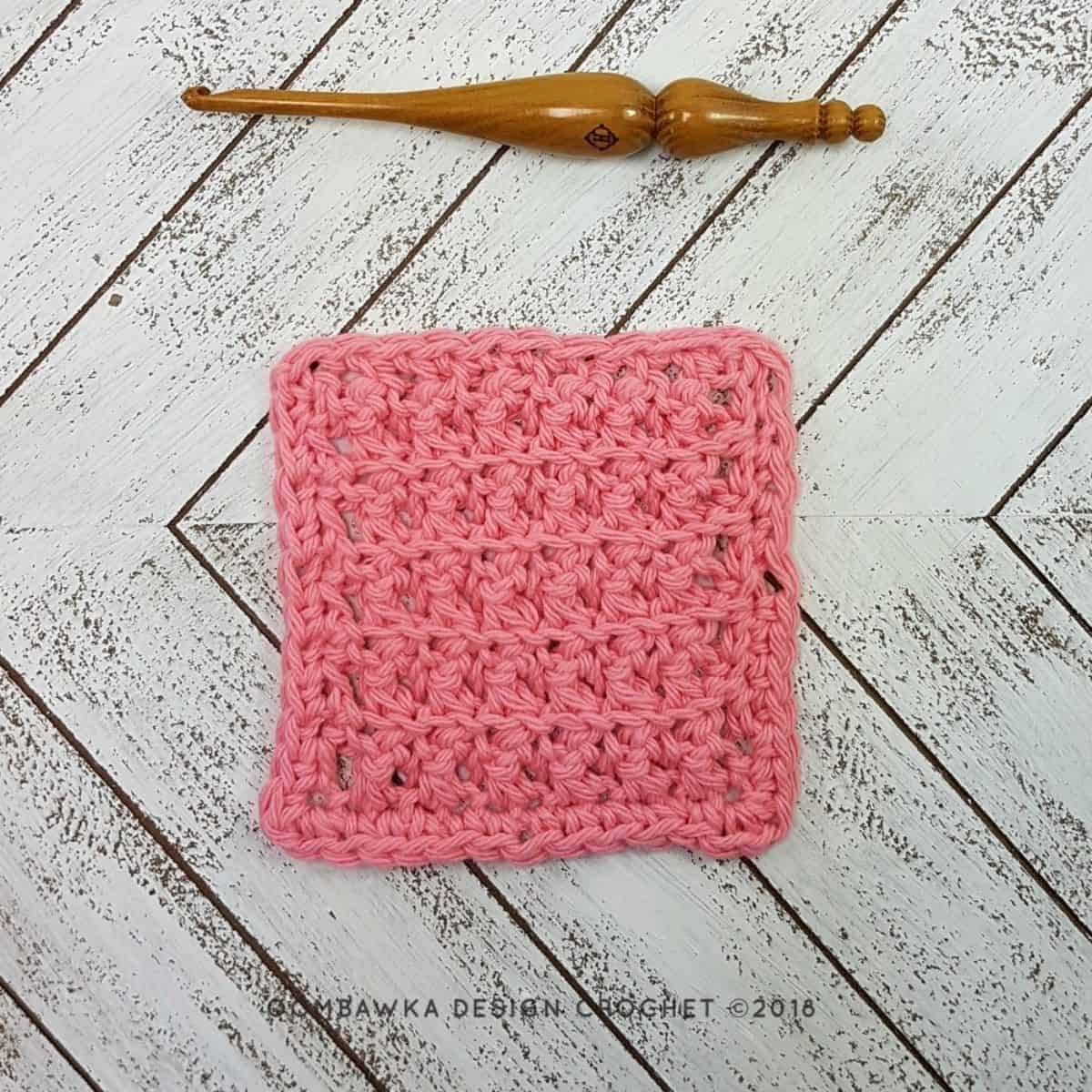 small pink square crochet stitches swatch laying flat next to a wooden crochet hook