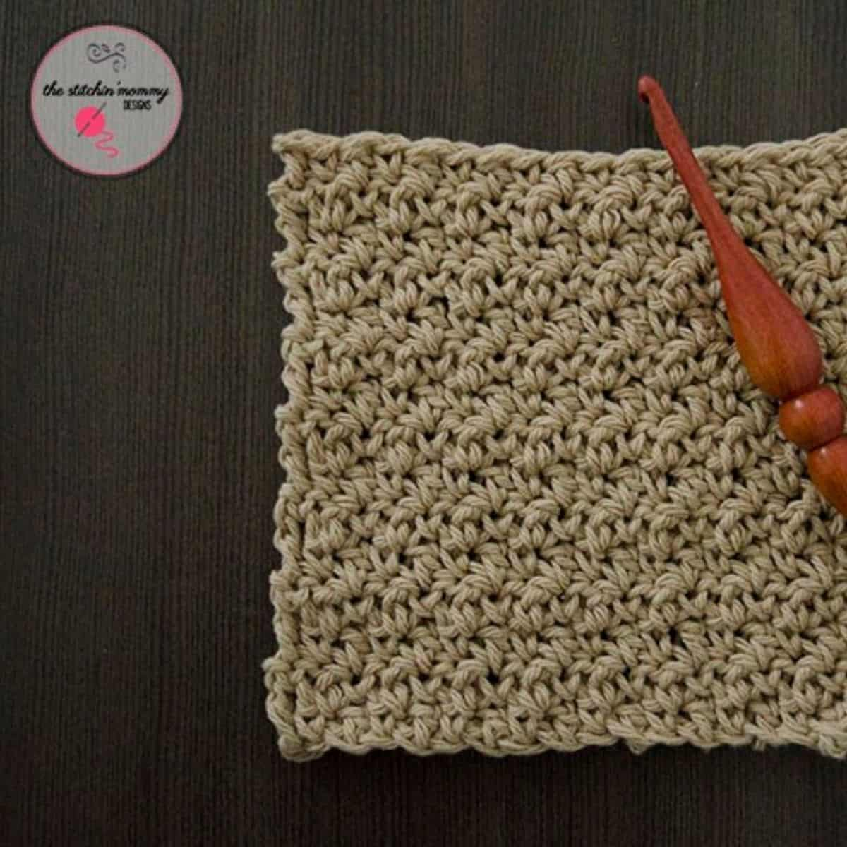 square seed stitch washcloth with a wooden crochet hook laying on top