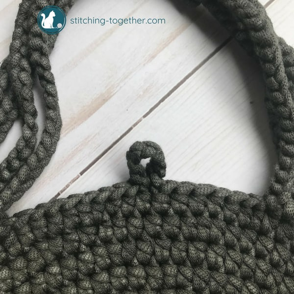 button loop on gray circle bag