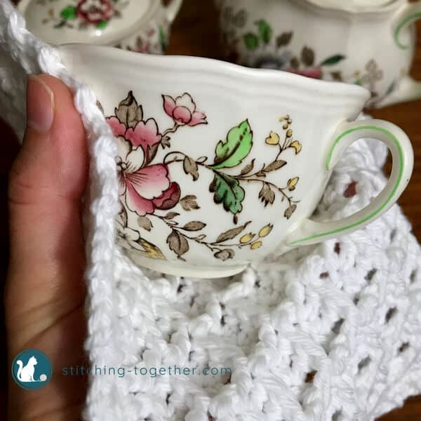 crochet waffle stitch dishcloth wrapped around a teacup