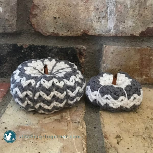 crochet pumpkins, gray and white, on brick