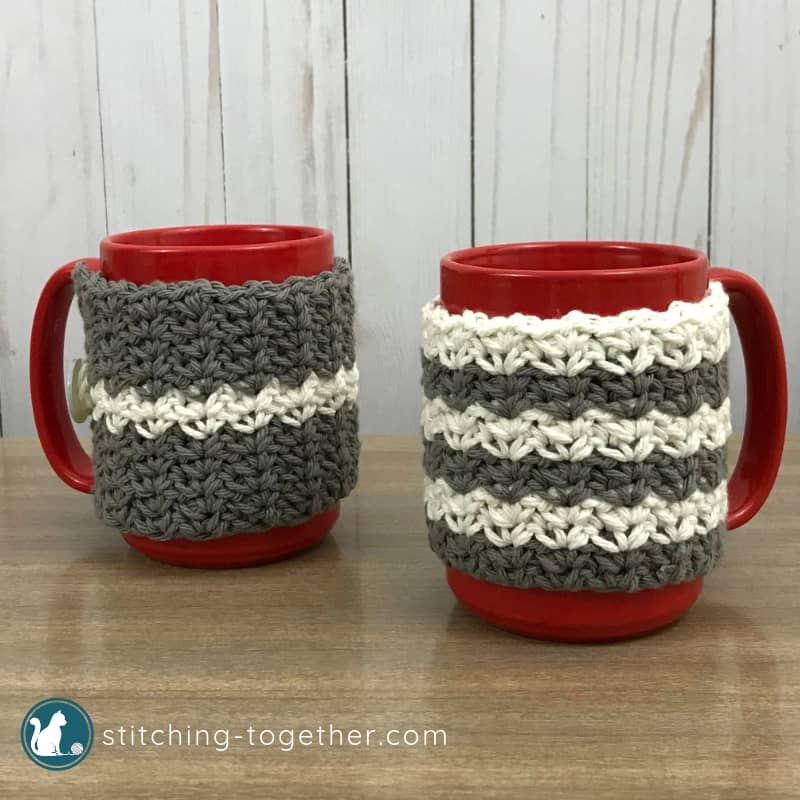 Two gray and white crochet coffee cup cozies