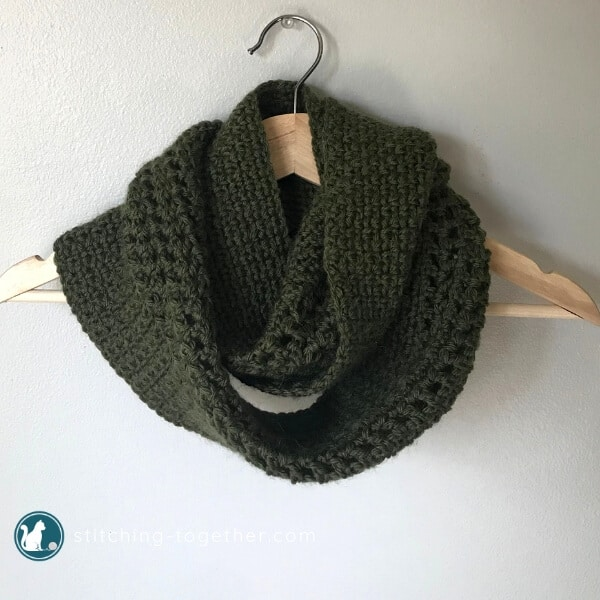 green crochet infinity scarf wrapped on a hanger