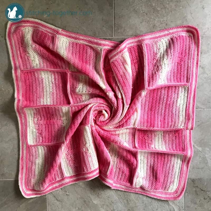 pink crochet blanket on the ground