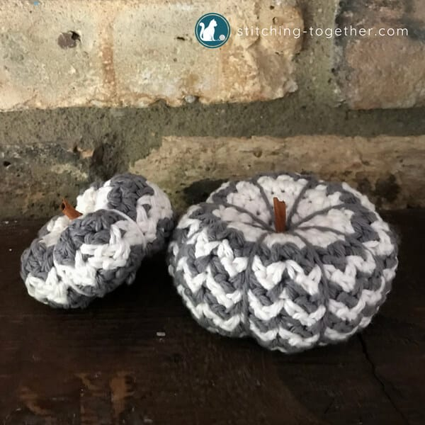 two gray and white crochet pumpkins - a mini crochet pumpkin and a small crochet pumpkin