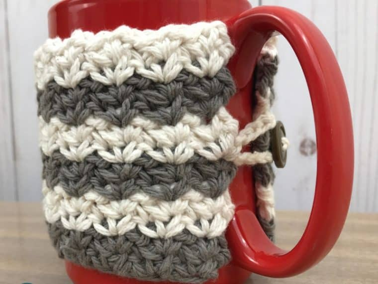 Close up of gray and white crochet coffee cup cozy
