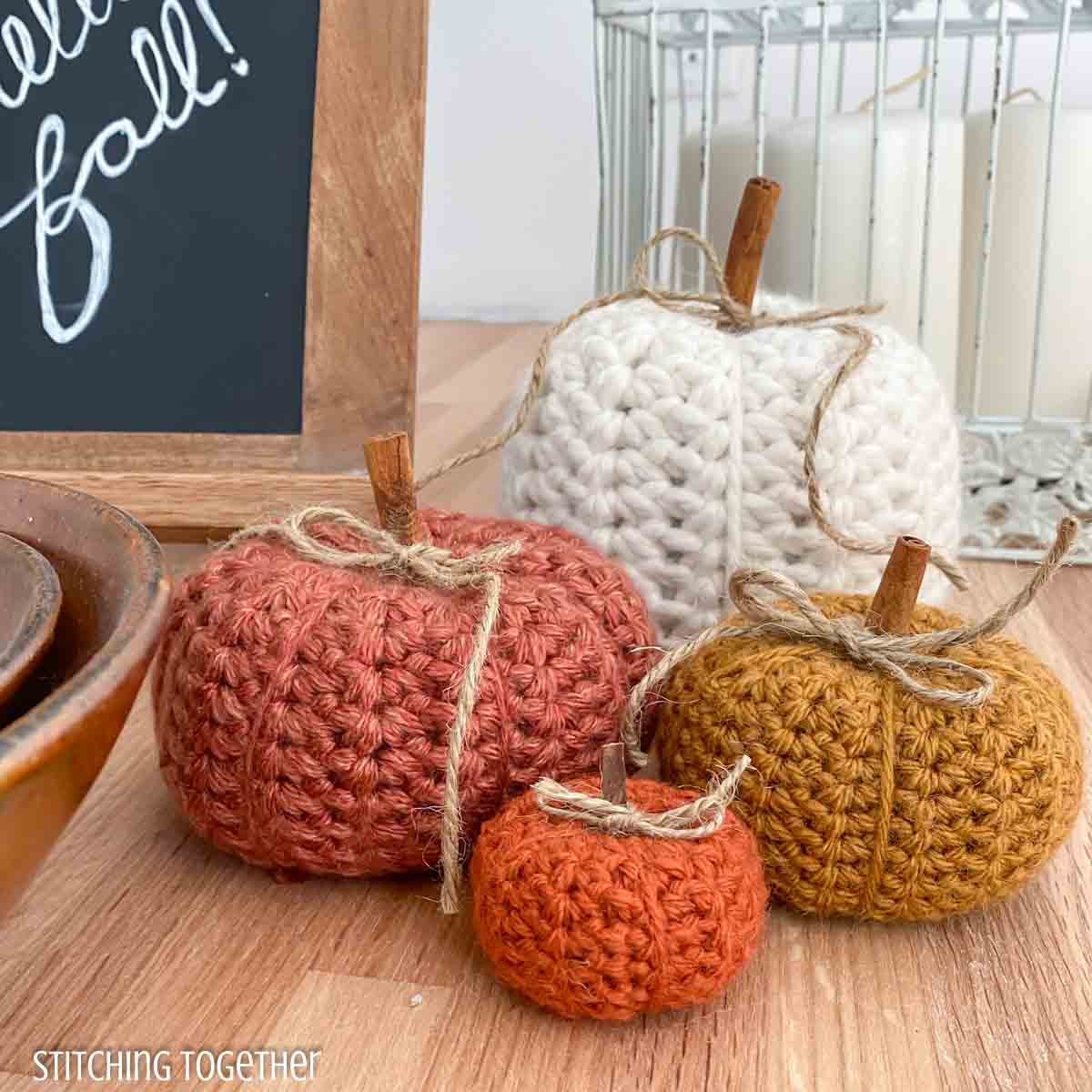 4 crochet pumpkins will surrounded by fall decor