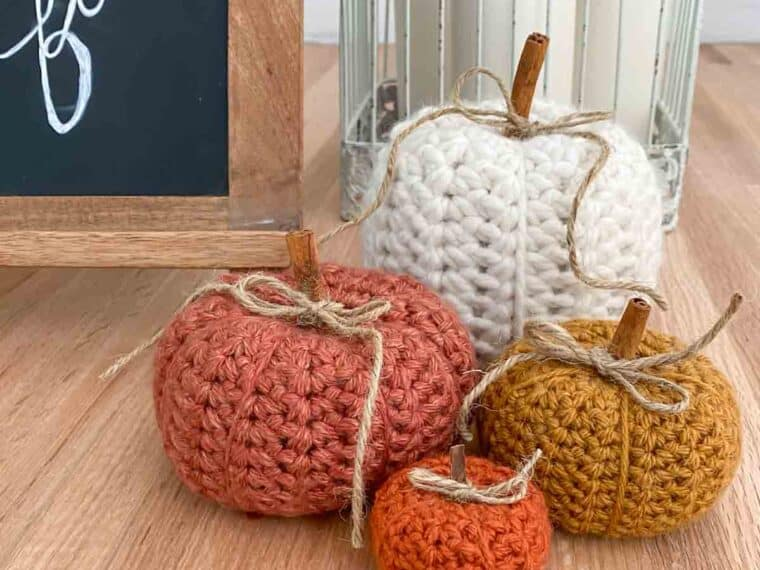 pumpkins crocheted and sitting next to a sign that says hello fall
