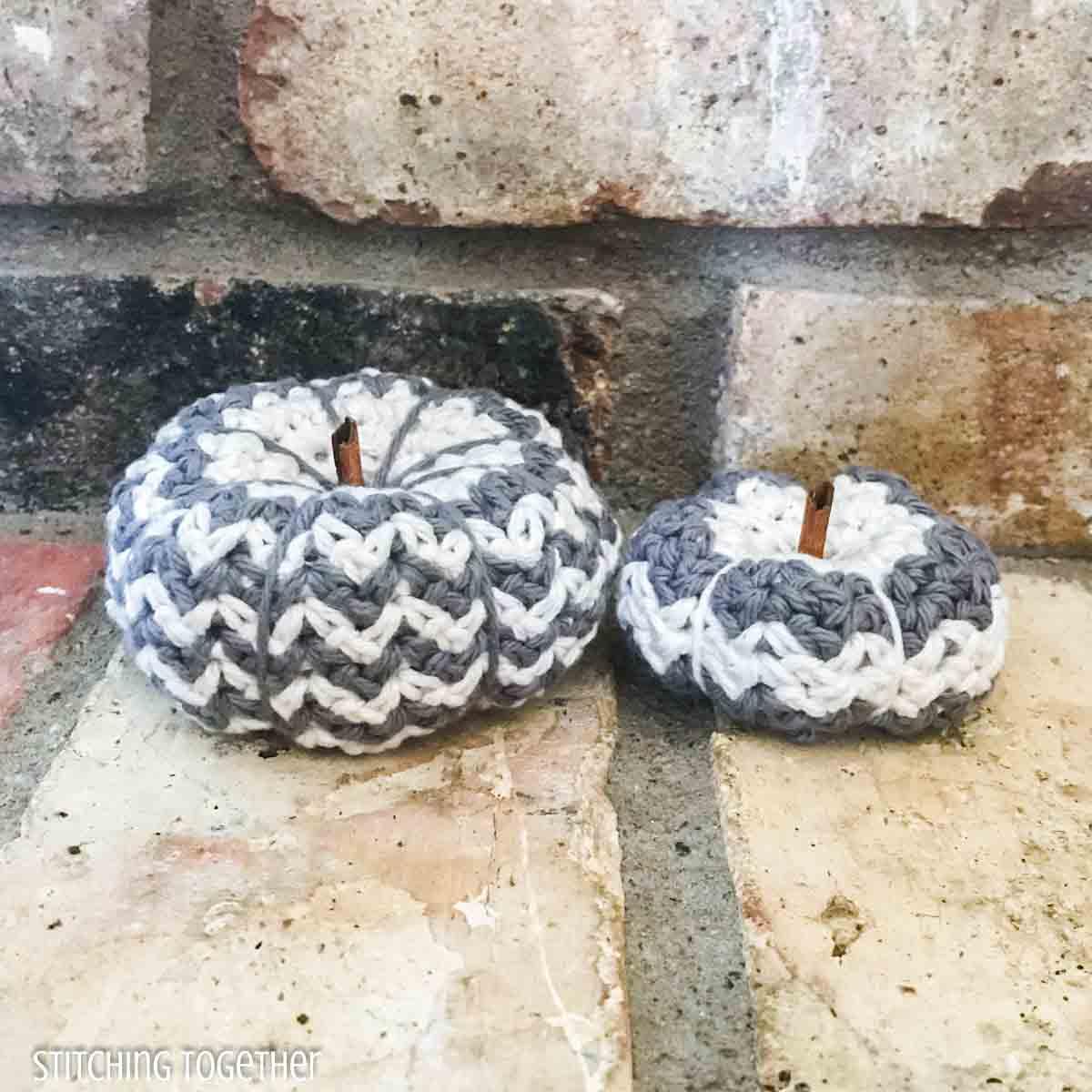 2 striped crochet pumpkins on brick