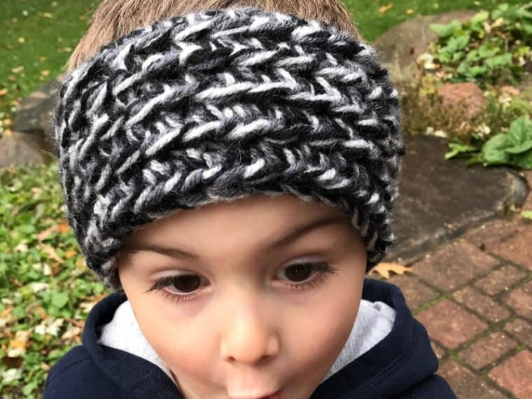 Boy wearing black and gray crochet ear warmer making a funny face