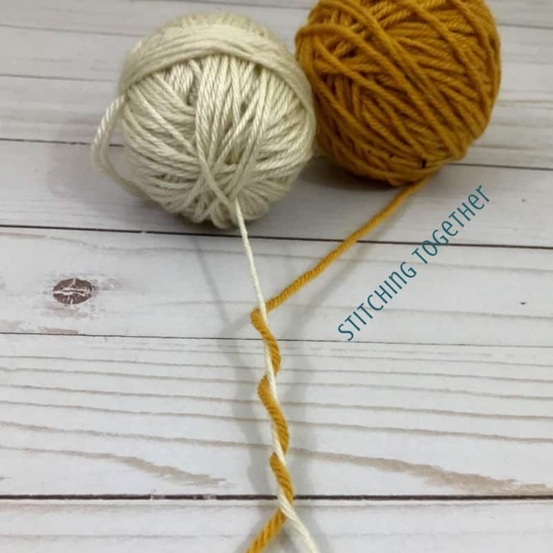 yellow and off white yarn wrapped around each other